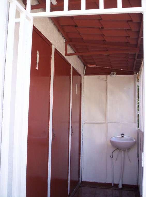 Servicios para damas y caballeros y un baño.